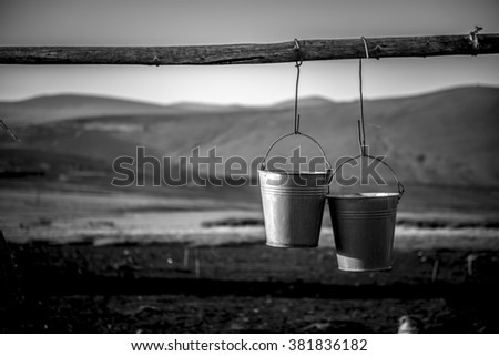 Pair of metal buckets hanigng from a rustic wooden beam
