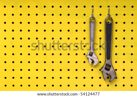 Pair of metal wrenches hang together off of hooks on yellow pegboard.