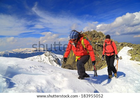 Pair of mountaineers climb a snowy trail on the mountain in winter
