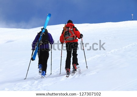 Pair of mountaineers climbing with skies on the mountain - stock photo