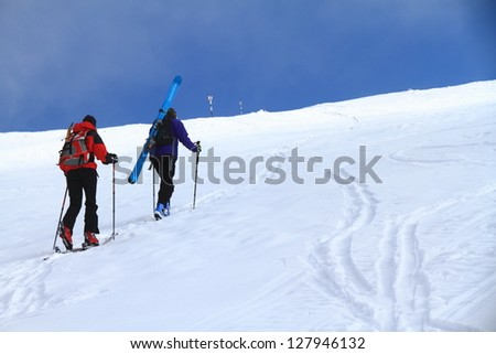 Pair of mountaineers climbing with skies on the mountain