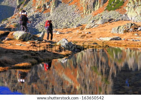 Pair of mountaineers passing a calm glacier lake - stock photo