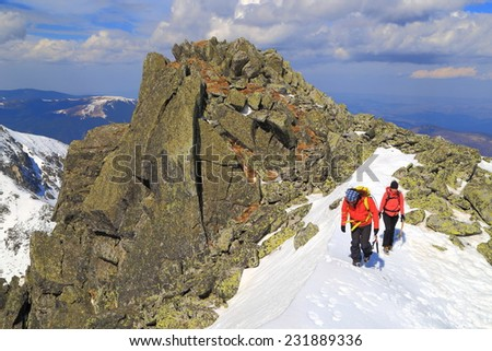 Pair of mountaineers walking on snow covered ridge in sunny winter day - stock photo