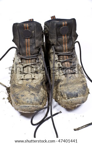 Pair of muddy , worn walking or hiking boots on a plain background - stock photo