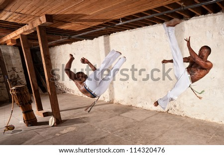 Pair of muscular capoeria martial artists performing techniques - stock photo