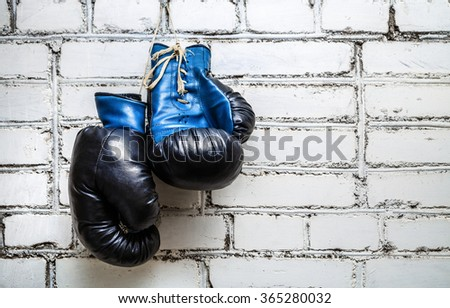 Pair of old blue boxing gloves hanging on white brick wall background. - stock photo