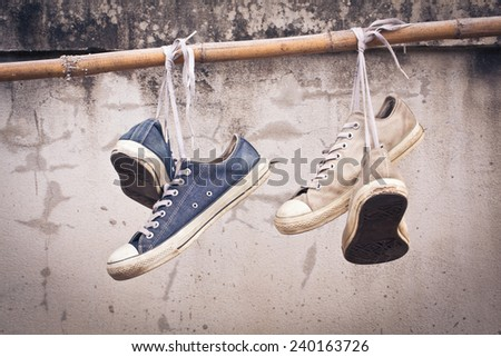 pair of old sneakers hang on bamboo, process color - stock photo