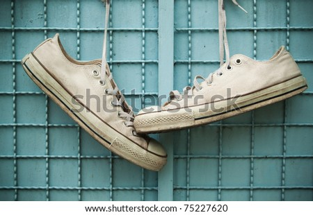 pair of old sneakers hang on blue wall - stock photo