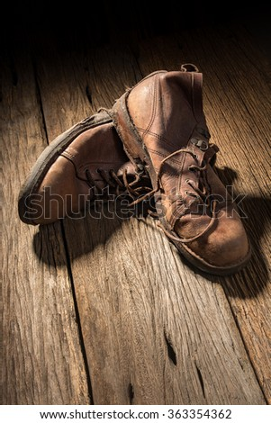 Pair of old used boots on rustic wood board