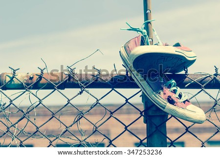Pair of old worn classic sneakers hang from rusty chain link fence - stock photo
