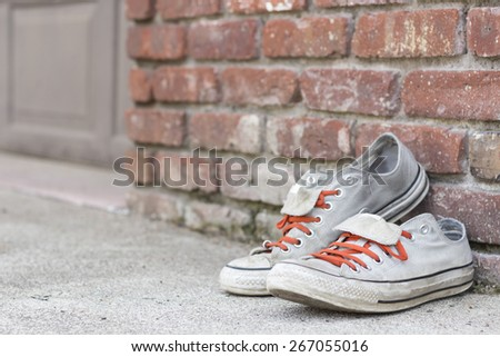Pair of old worn classic sneakers leaning against a brick wall - stock photo