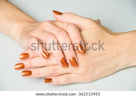 Pair of open female hands with brown metallic paint on fingernails resting on white background