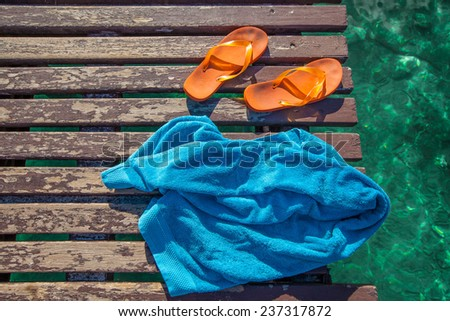 pair of orange flip-flops and a blue towel on the wooden planks of a jetty over the sea - stock photo