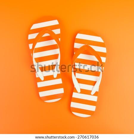 Pair of orange striped flip flop on orange background - stock photo