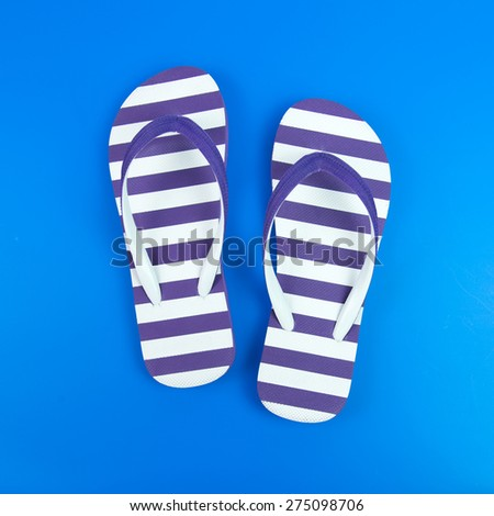 Pair of purple striped flip flop on blue background - stock photo