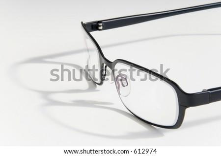 Pair of reading glasses, closeup & white background - stock photo