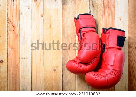 pair of red boxing gloves hanging on the wall - stock photo