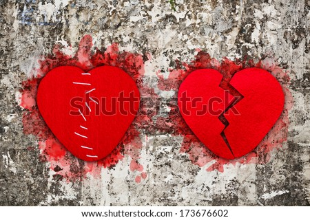 Pair of red broken hearts on aged wall texture  - stock photo