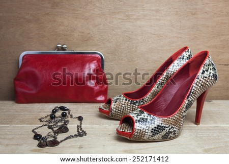 Pair of red snake shoes and red handbag  - stock photo