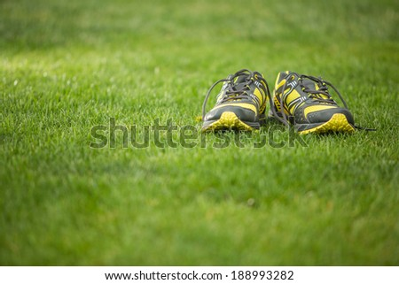 Pair of running shoes on green grass - stock photo