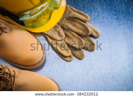 Pair of safety lace boots leather gloves hard hat and transparent plastic glasses on scratched metallic background construction concept. - stock photo