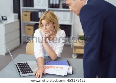 Pair of serious young blond business people looking over charts and their laptop computer at office with binders on bookshelves in background - stock photo