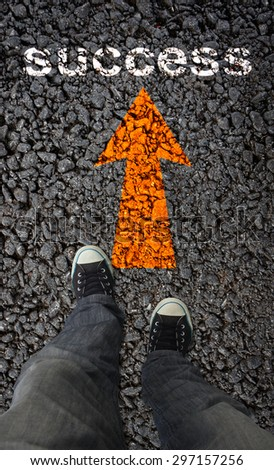 Pair of shoes on a road with yellow arrows with SUCCESS - stock photo
