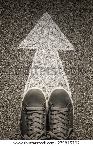 Pair of shoes standing on a road with arrow - stock photo
