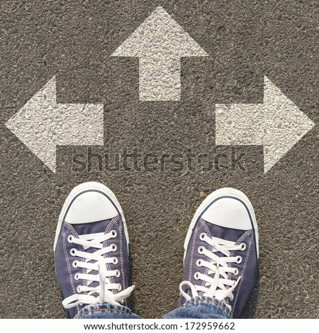 Pair of shoes standing on a road with three white arrow - stock photo