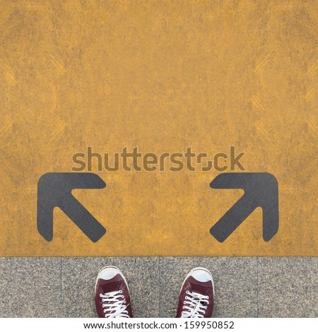 Pair of shoes standing on a road with two grey arrow on the yellow background - stock photo