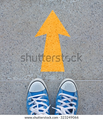 Pair of shoes standing on a road with yellow arrow on concrete background - stock photo
