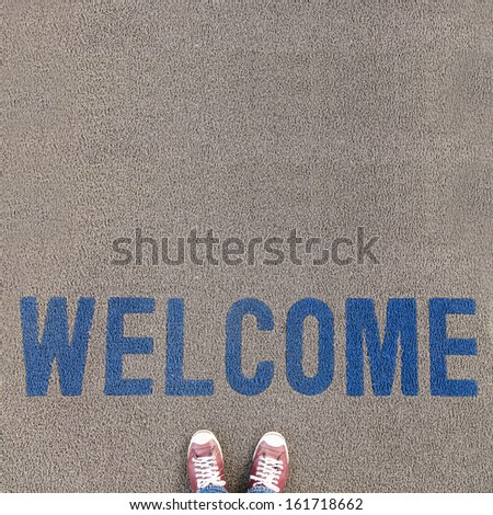 Pair of shoes standing on carpet walkway with WELCOME text - stock photo