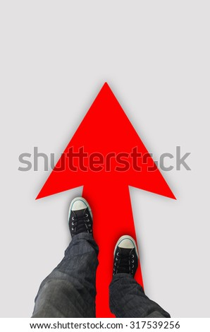 Pair of shoes standing with red arrow on the white background - stock photo