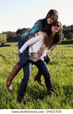 pair of sisters in the field - stock photo