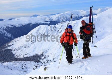 Pair of ski mountaineers on the summit - stock photo