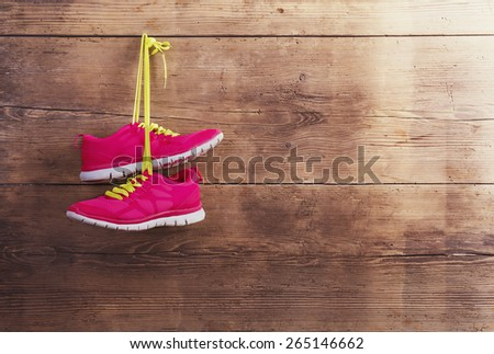 Pair of sneakers hang on a nail on a wooden fence background - stock photo