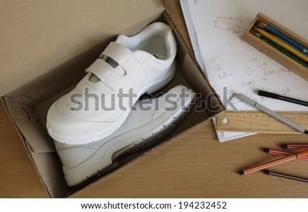 Pair of sneakers in shoe cardboard box on student table. - stock photo