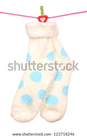 Pair of socks with polka dots hanging on a rope isolated on white - stock photo
