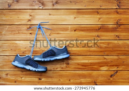 pair of sport shoes hang on a nail on a brown wooden wall - stock photo