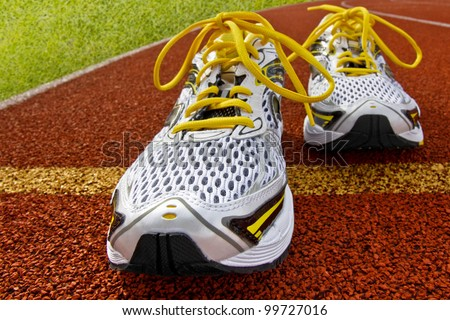 Pair of sports shoes standing on a tartan race track - stock photo