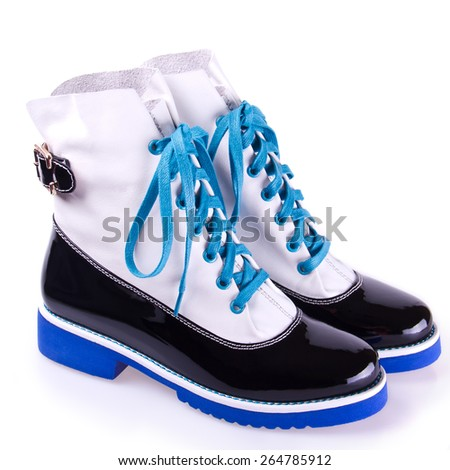 pair of stylish women's black and white shoes with blue laces and soles, isolated on white - stock photo