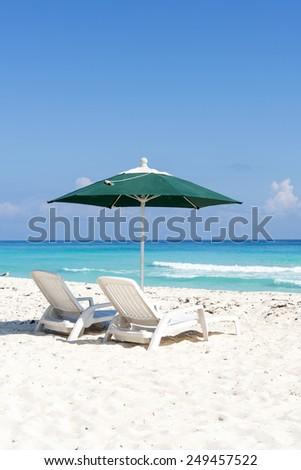 Pair of sun loungers and umbrella on a tropical beach in Cancun, Mexico. - stock photo