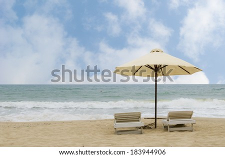Pair of sun lounges and a beach umbrella on a deserted beach - stock photo