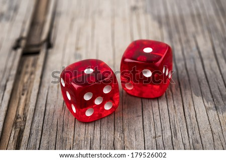 Pair of thrown red dices on old wooden table showing two ones - snake eyes - stock photo