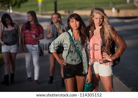 Pair of tough young female students standing outside - stock photo