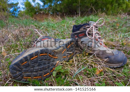 pair of touristic boots in a grass - stock photo