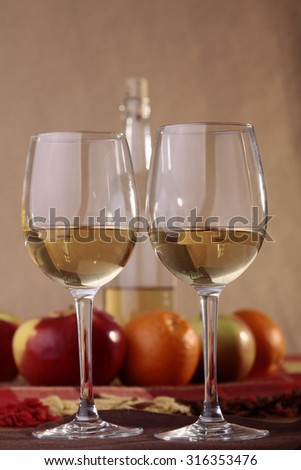 Pair of transparent glasses half filled with white sweet amber wine with open incomplete bottle ripe apples oranges on table covered with plaid, vertical photo - stock photo
