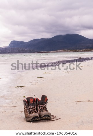 Pair of trekking shoes on a remote beach with sea and mountains in the background. - stock photo