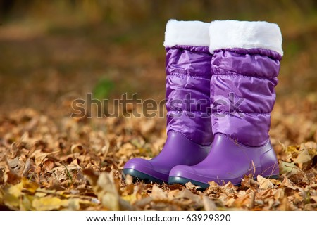 Pair of violet female boots with white edging in autumn foliage - stock photo