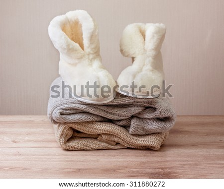 Pair of warm winter sheepskin slippers (alpaca)  on  pile of warm woolen clothes (Selective focus) - stock photo